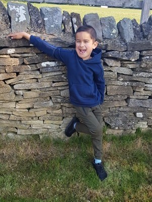 Boy wearing junior flex shoes leaning against a wall