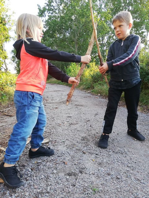 boy and girl in citee junior fighting with sticks